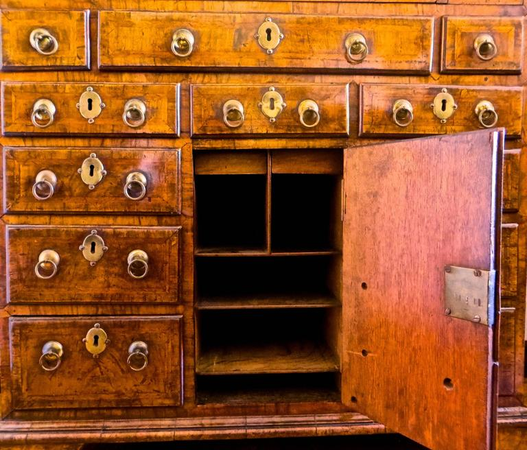 The discerning collector will find this museum quality bachelors chest quite appealing, with its unique and one of a kind drawer and cupboard configuration. This is from the Thomas Devenish Collection (documented see provenance). An important piece