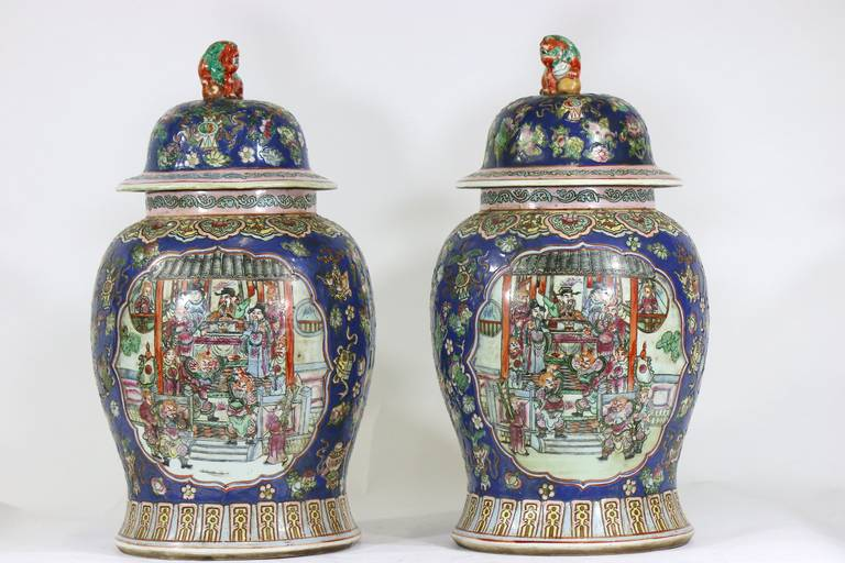 A stunning cobalt blue pair of famille rose Chinese porcelain ginger jars urns with foo dog covers, decorated with figures and animals in a mountain and sea landscape, banded pattern at base and shoulder, Qianlong mark on base. Provenance: