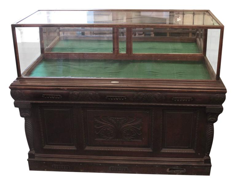 1800s carved oak framed cigar humidor with oak glass showcase on top by Whitcomb Cabinet Co. Features beveled glass with two pull down mirrored doors. The base is the humidor, and the brass vents are on the front and back. There are drawers and