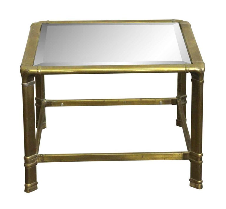 1970s brass frame end table with beveled glass done in a Mid-Century Modern style. The pin to secure the glass on the bottom needs work, therefore the bottom glass is not pictured. There is a chip in the bottom glass piece as well. This can be seen