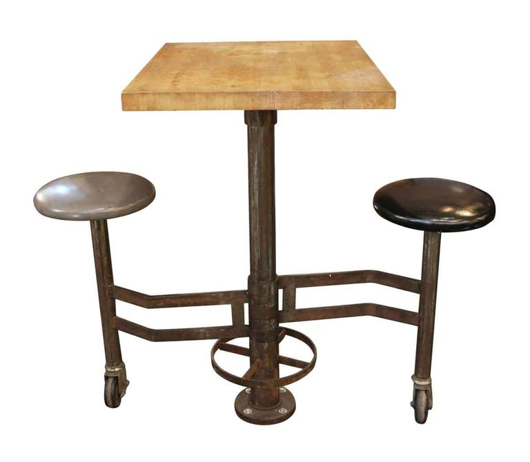 1980s counter height industrial base table made of cast iron and butcher block wood with unusual attached rolling vinyl covered seats. One seat is gray and the other is black. The seats are attached to a center pedestal and freely move on a wheeled