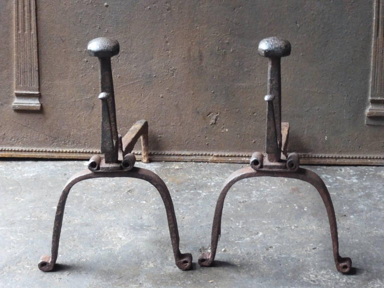 18th century Gothic style fire dogs made of wrought iron. The andirons have spit hooks to grill food.  We have a unique and specialized collection of antique and used fireplace accessories consisting of more than 1000 listings at 1stdibs. Amongst