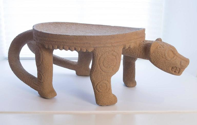 Estate of Joseph Paul and Billie Schaumberg, Santa Fe, NM.  Diquis culture   Carved gray volcanic stone metate in the form of a stylized jaguar having a curled tail type rear handle and a projecting head. Standing on four tapered legs carved