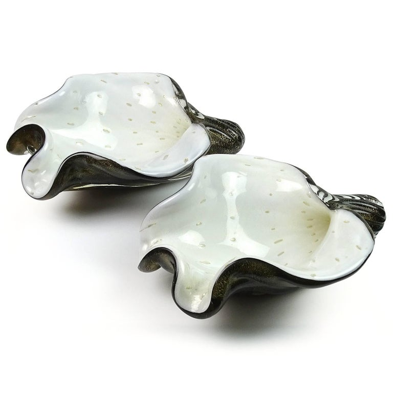 Beautiful set of two Murano hand blown black, white, controlled bubbles and gold flecks art glass seashell sculptural bowls. Documented to Alfredo Barbini, circa 1950s. Perfect for a Nautical or Ocean themed room. Priced as a set, but can be sold
