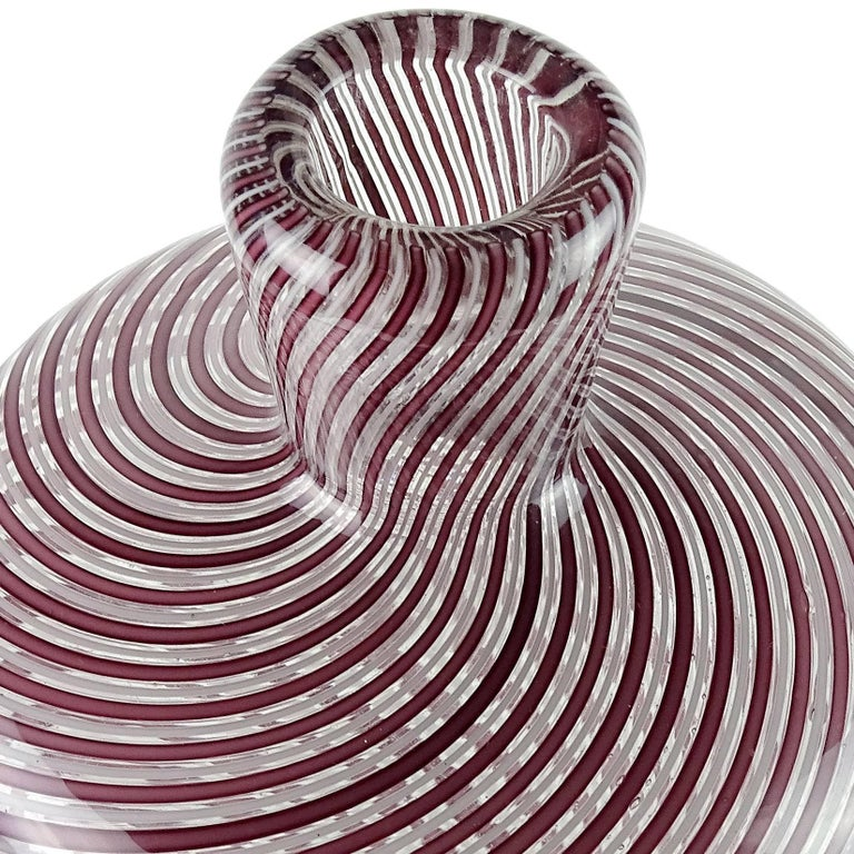 """Beautiful Murano hand blown purple and white ribbons art glass corset flower vase. Attributed to designer Dino Martens for Aureliano Toso. The piece has an optic swirl design, with cinched in body. Measures 10 3/4"""" tall x 4 1/2"""" wide."""