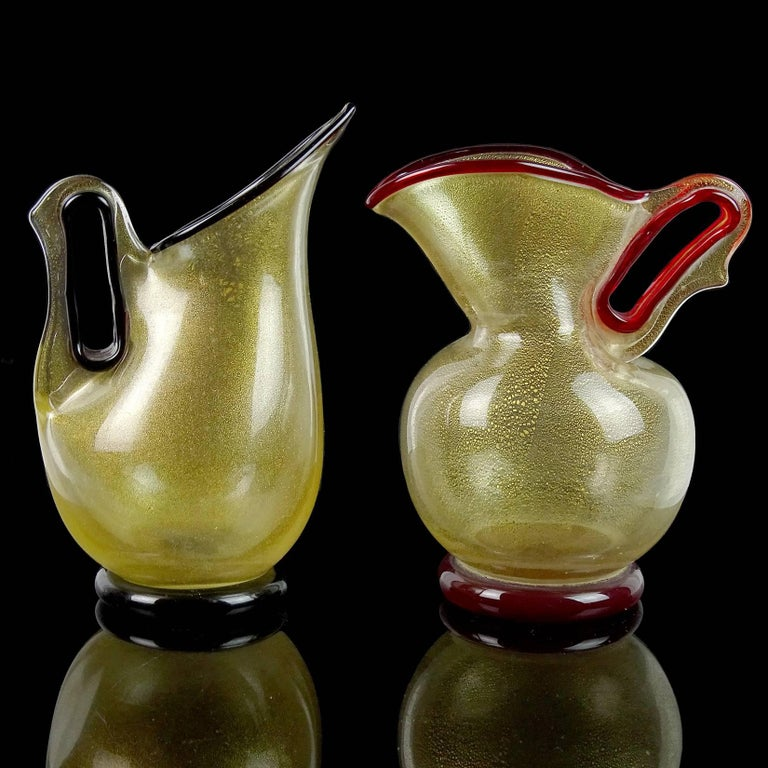 Beautiful and rare Murano hand blown red trim and dark purple trim Italian art glass pitcher shaped vases with gold flecks. Documented to designer Ercole Barovier, for the Barovier e Toso company. Designed in shapes from the