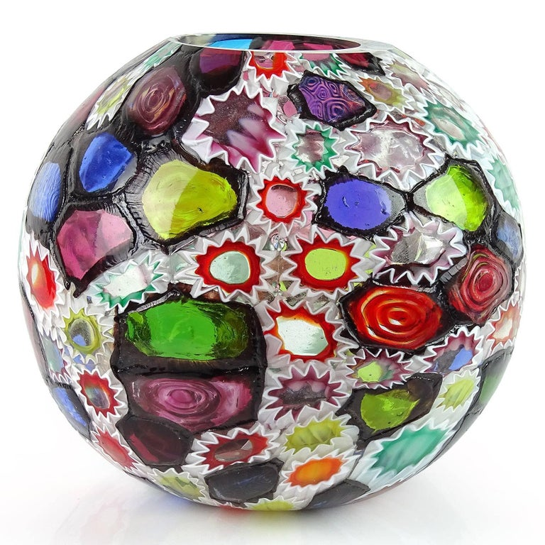 Gorgeous Murano hand blown multi-color Millefiori flower and star mosaic Italian art glass flower vase. Documented to the Fratelli Toso company. Many of the murrines are lined in white, while others are lined in metallic black. Rare that it has so