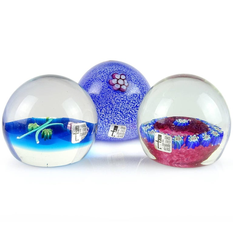 Beautiful set of Murano handblown flower design Italian art glass paperweights. Documented to the Fratelli Toso Company, all with original labels. Top paperweight has a melted overshot surface with purple and white flower murrines. Second has