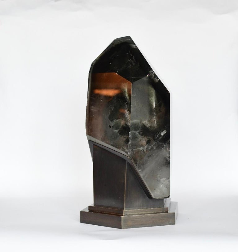 A diamond form rock crystal sculpture light. A million years old rock crystal that encases the top of a mountain over the clouds. An abstract work of nature.  Antique brass finish base. Created by Phoenix Gallery.