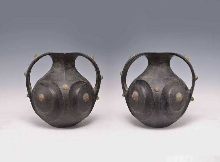 Frontal view of black pottery Amphora with two handles and mouth with two angular spouts. Round metal decoration applied around the body and handles. Original patina with natural mineral calcification. Han Dyansty 220BC.