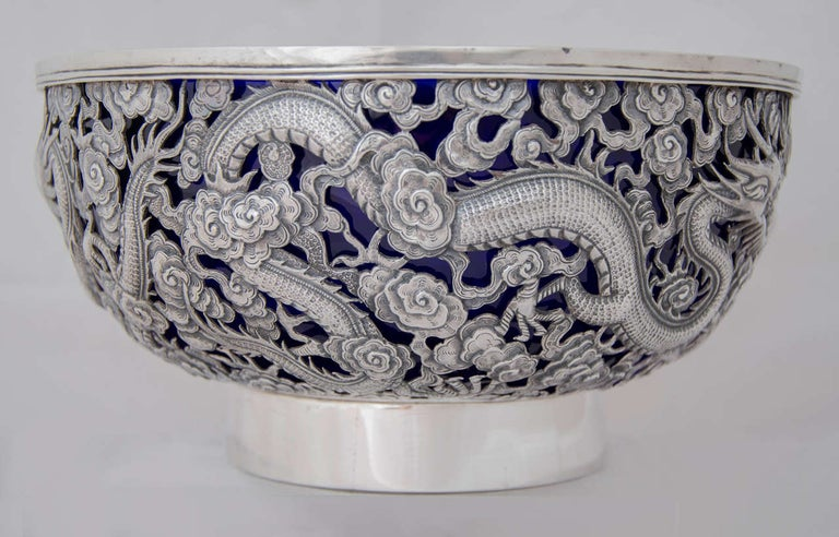 A large Chinese export silver bowl, beautifully pierced with two opposing dragons separated by a flaming pearl, and a third dragon breathing fire. 