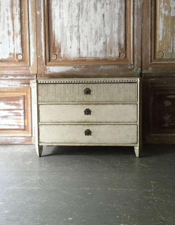 Late Gustavian period chest of drawers with fluting on front of the upper drawer. Shaped top with dental trim under, reeded canted corners and classical feet. Very classical Swedish piece with original charming hardwares,
