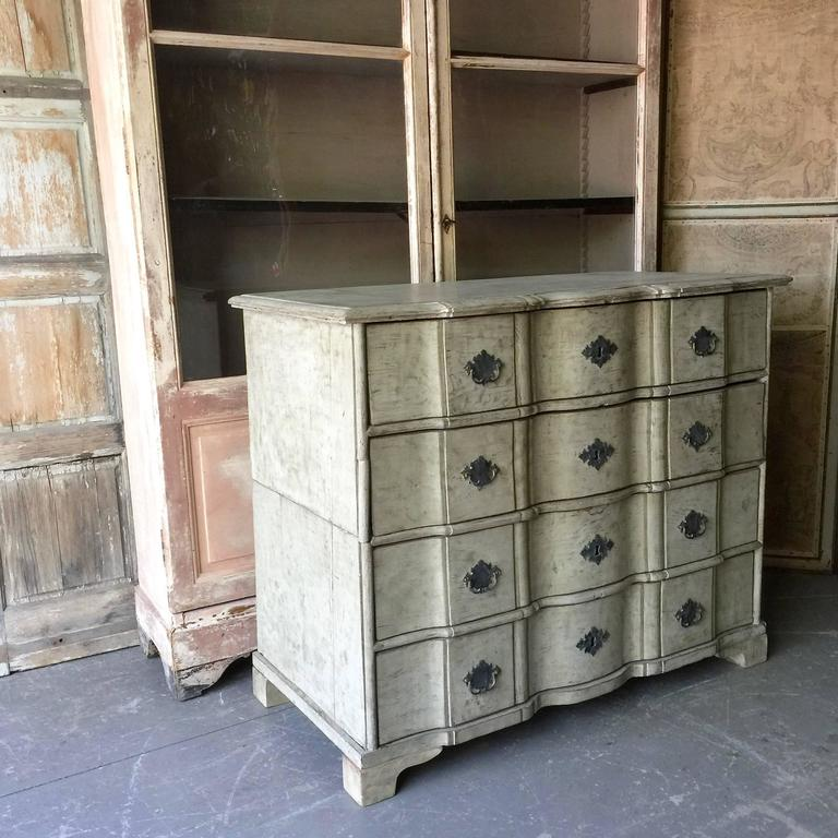 19th century chest of drawers in richly carved scraped to original painted oak with curvaceous serpentine drawer fronts, handsome bronze hardwares and shaped top, Denmark, circa 1880. The chest is in two parts for convent travels. Here are few