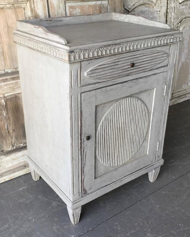 A caharming Swedish Late Gustavian side cabinet/ large nightstand with wonderful white/cream time-worn patina, classic proportions with carved paneled door and drawer with a large reeded oval in center, gallery top and tapered legs.
