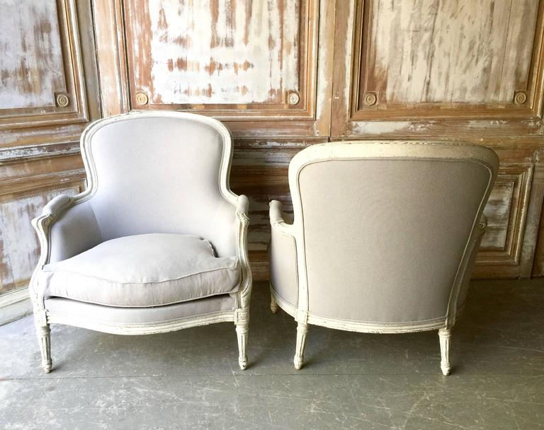 A pair of 19th century French bergères in Louis XVI style. The wood frames are in white/gray painted finish, the top gracefully curved, the seat rails and the cabriole legs with florets. Completely re-upholstered in linen/cotton fabrics and down