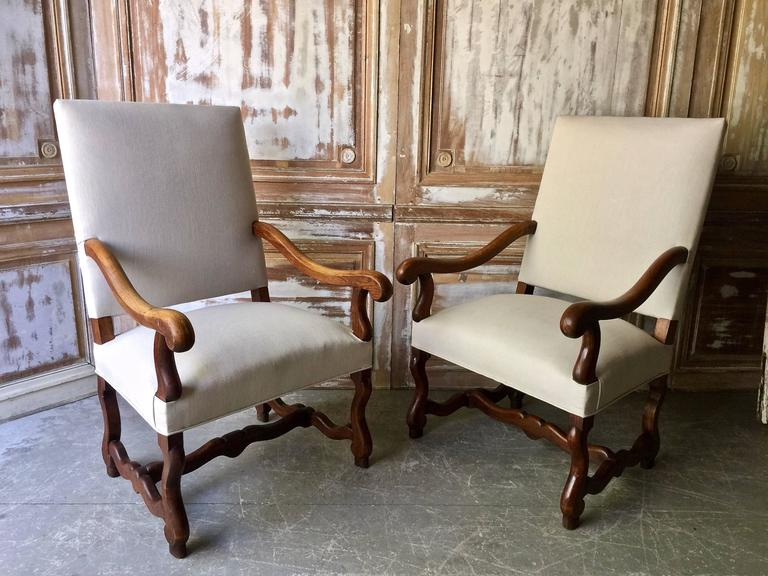 A large pair of French Fauteuil with billhead arms (bec de corbin) and H-shaped mutton-bone stretcher (os de mouton) in beautifully patinated oak. Upholstered in modern time linen. Very comfortable large chairs, France, circa late 18th