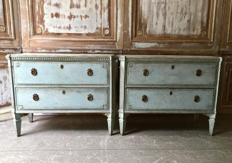 A very handsome pair of 19th century Swedish Gustavian style chests in charming pale blue paint with contrasting marbleized wooden tops. Drawers with raised panels and bronze hardwares.