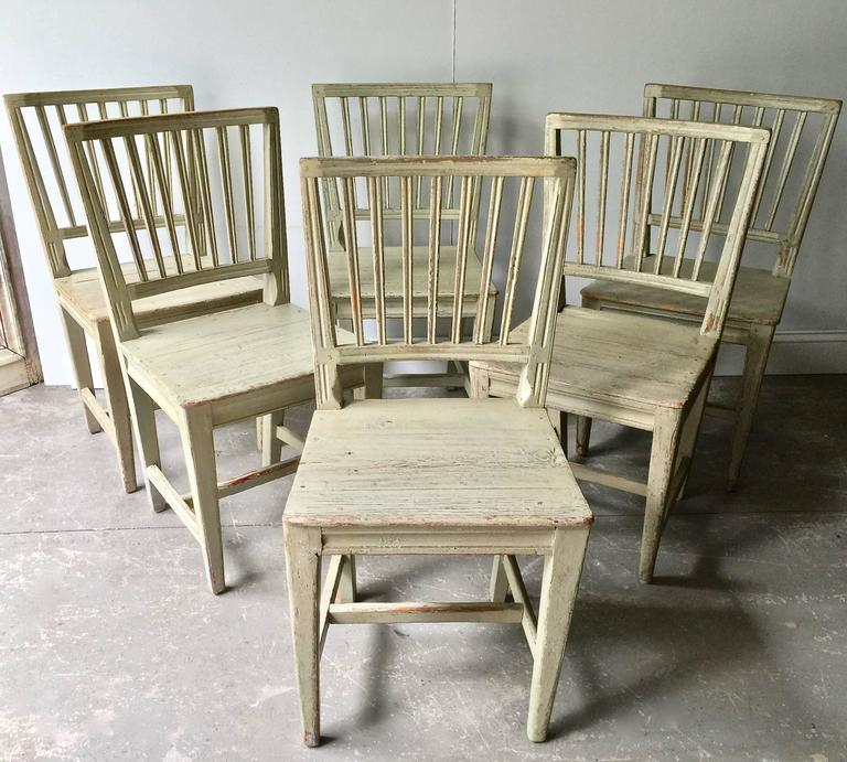 A charming set of six of Swedish 19th century painted Primitive side chairs with simple baluster backs, shaped aprons and straight legs with H-stretchers in time worn greenish patina with traches of bluish paint,
