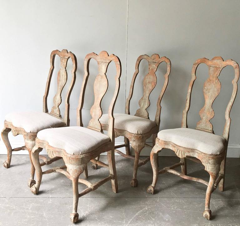 Set of four elecant18th century Swedish chairs in Rococo period, circa 1760. Lovengly handmade with ritchly carved. Hand scraped back to traces of their original worn paint. Upholstered with antique raw linen. Very elegant chairs, look fantastic