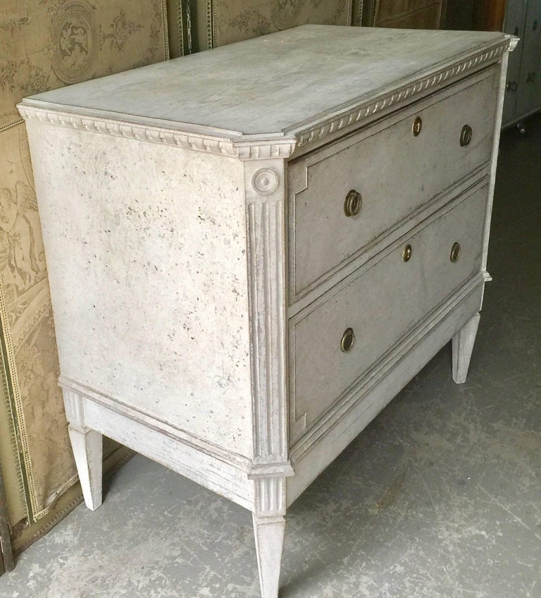 Early 19th Century Swedish period Gustavian chest of drawers with brass fittings, shaped top and canted corners posts with fluted and medallion details.  Sweden, circa 1810. More than ever, we selected the best, the rarest, the unusual, the