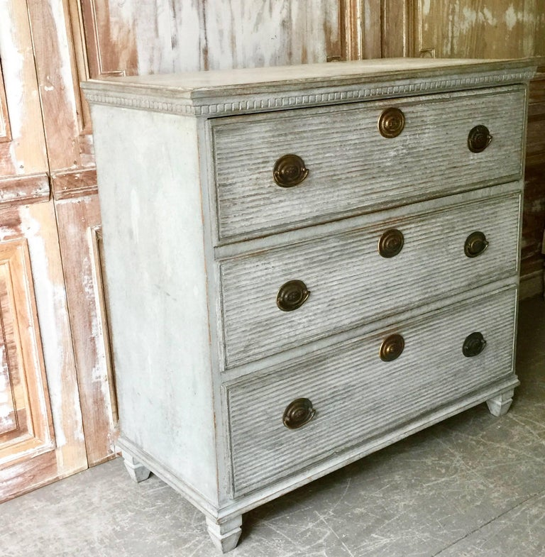 Swedish early 19th century chest of drawers with three horizontal reeded drawers, and small bank of drawer inside of upper drawer. Handsome hardware's and dentil molding in blueish, gray or greenish color under the shaped top, Sweden, circa