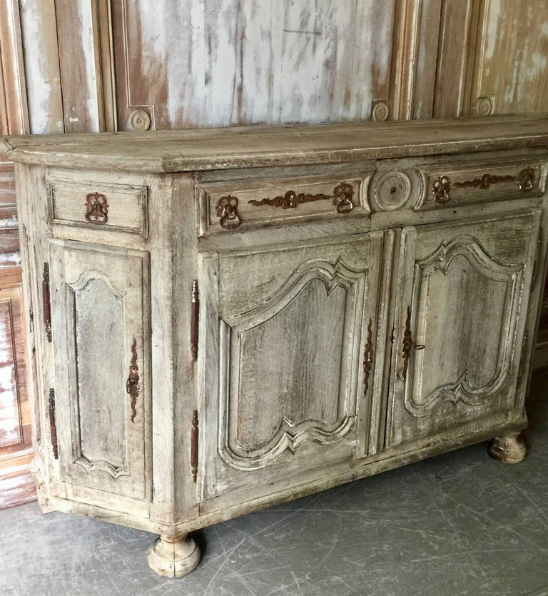 Handsome 18th century French enfilade or sideboard, in Louis XV manner with shaped top and richly carved fielded door panels on front bun feet in superb patinated natural oak. Original rustic ironwork. France, late 18th century. More than ever, we