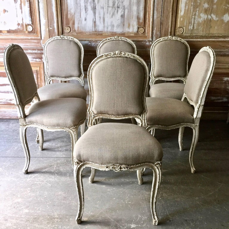 Set of six decoratively carved French Louis XV style chairs, scalloped frieze carved in floret motifs raised on cabriole legs. Upholstered in pale grey linen.