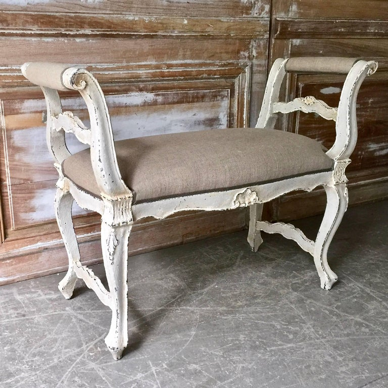 A small, elegant French LXV style banquette with cabriole legs and foliate carving at the knees, armrests and centre of the seat rails, France, circa 1900.