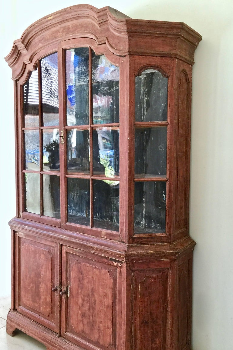 A very handsome 18th century Dutch cabinet vitrine in impressive scale with original handblown glass, scaped to most original patinated color, beautifully shaped/scalloped interior shelves, arched pediment cornice and panelled doors.