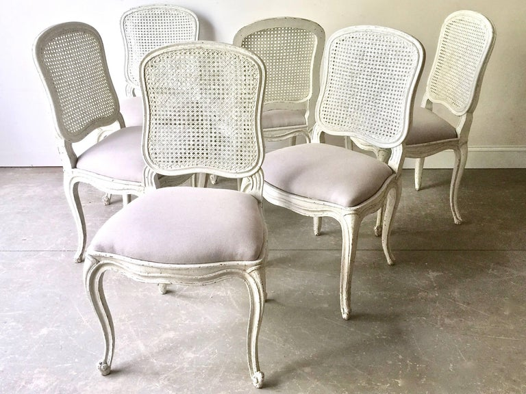 "Set of six French, 19th century dining chairs Louis XV style with flat back called ""la Reine"" is caned and scalloped frieze carved and raised on cabriole legs. Newly upholstered in light gray linen. Seats are removable for easy re-uphostery. Very"