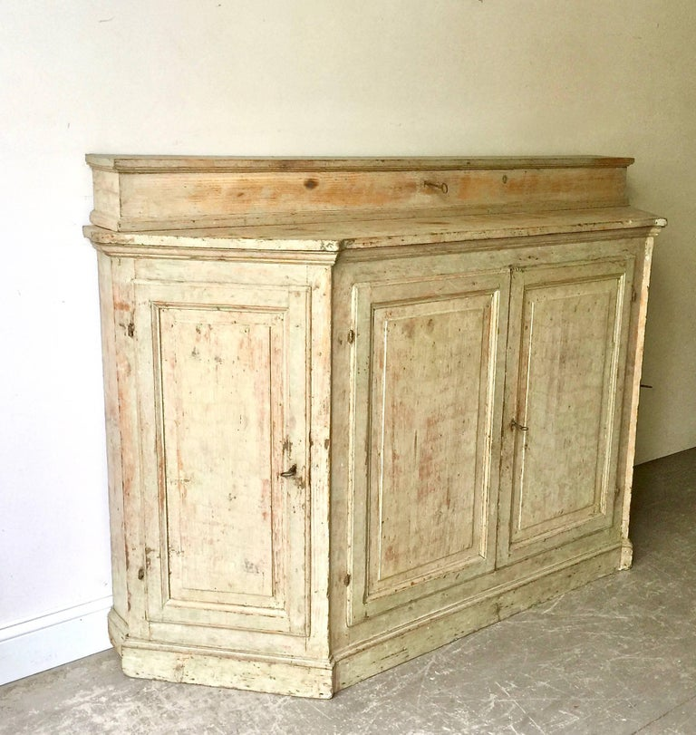 A rare four-door 18th century Italian Credenza with angled panelled doors at each corner and panelled central doors under the shaped top with unusual long lockable storage box. All in superb patinated greenish/blue original color.