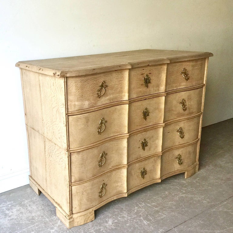 18th century Danish chest in two parts with four deep drawers from late Rococo period in richly carved bleached oak with curvaceous serpentine drawer fronts, shaped top and bracket feet. 