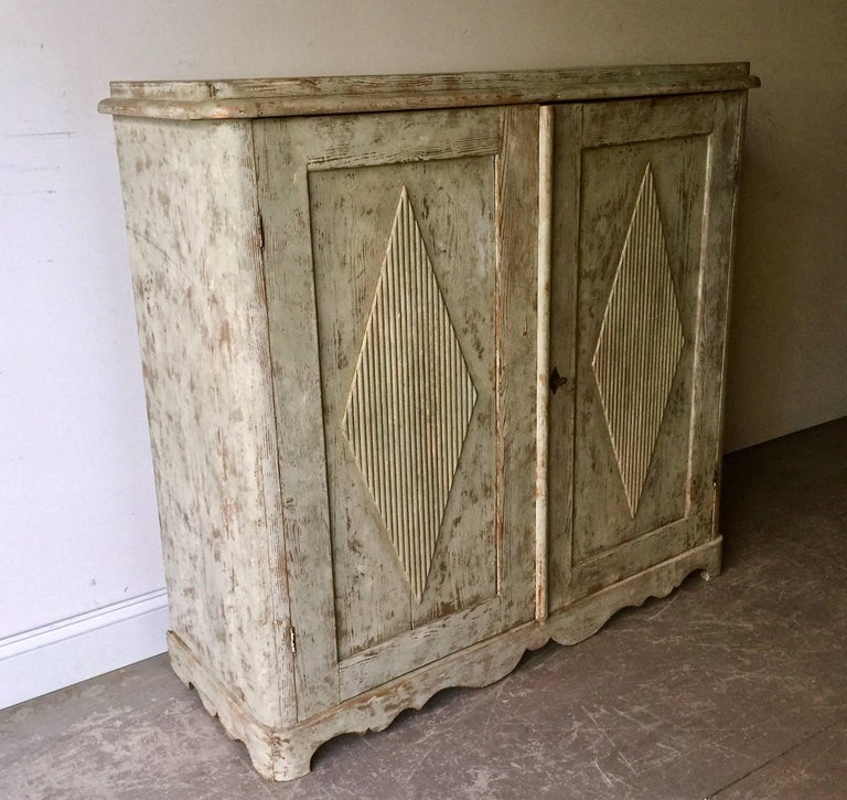 19th century Swedish Gustavian sideboard with classic Gustavian motifs; diamond shaped panelled doors on beautifully scallop-shaped apron. Inside with two shelves and two drawers. Scraped back to remnants of its original cream/greenish/ paint.