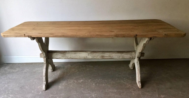 """19th century Swedish trestle table in style in """"Allmogestil"""" country folk customs and traditions cherished of the native traditions and folk culture. A rustic family table with wonderful old worn patina with worn pine top on painted x-shaped legs"""