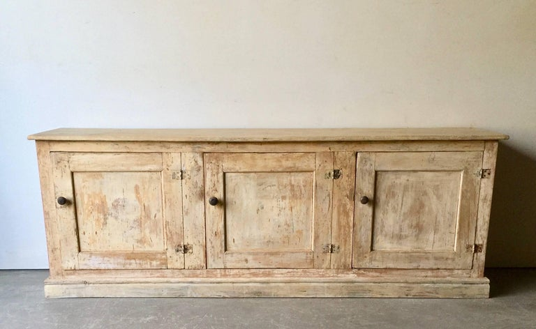 A large three door 19th century Italian sideboard in original lot of time worn patina with amble storage.  Surprising pieces and objects, authentic, decorative and rare items. Discover them all.