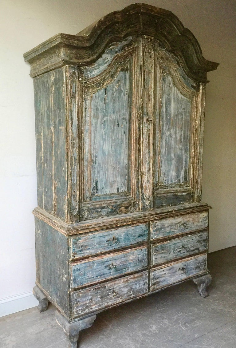 Original deep blue patinated 18th century Swedish Rococo period cabinet from Manor House, Stockholm, with wonderful arched cornice, original hardware, features two shelves and a notched spoon shelf in worn salmon color patina supported with