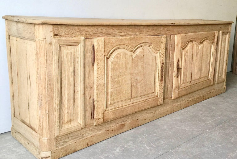 Handsome, long 19th century French sideboard, in Louis XV manner with shaped top and two richly carved fielded door panels in superb patinated natural oak. Original rustic ironwork. 
