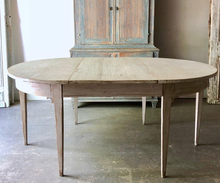 Early 19th century painted Gustavian period extending table with two leaves and tapered legs. A practical piece that can be used as round table or extended with one or two leaves up to 92
