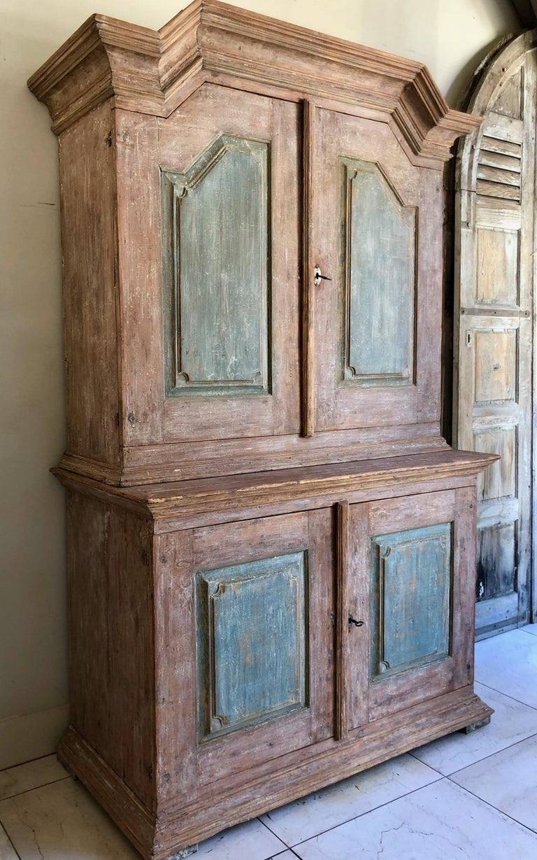 A very fine example of early 18th century two part cabinet of Gustavian period with a high arching pediment cornice and ritchy blue painted panelled doors on flat feet. Dalarna, Sweden, circa 1780.  More than ever, we selected the best, the