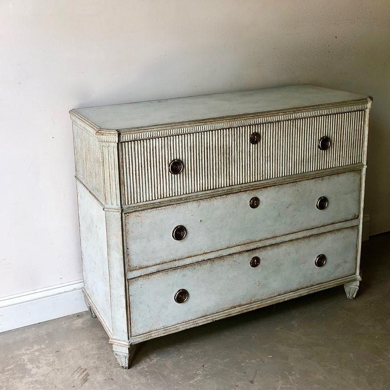 Late Gustavian period chest of drawers with fluting on front of the upper drawer. Shaped top with dental trim under, reeded canted corners and classical feet. Very classical Swedish piece with charming hardwares in pale blue. Sweden, circa 1810.