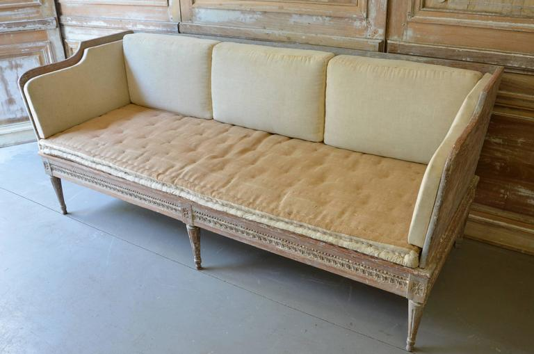 """18th century Swedish Gustavian period """"Trågsoffa,"""" finished on three sides with leaf rod and floral rosette medallions above reeded legs. Scraped to original cream white/blue finish. Original cussions ready for new upholstery. Stockholm,"""