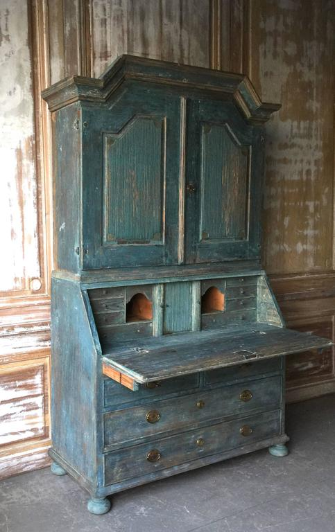 A very fine example of early 19th century secretaire cabinet of Gustavian period with a high arching pediment cornice and reeded panelled doors. The fall front desk with multitude of drawers and compartments in wonderful sky blue paint over the