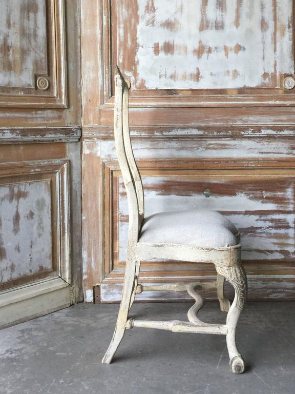"""18th century Swedish chair, in Rococo period, circa 1760. Lovengly handmade with rocaille carving on the seat rails and pierced splats. Hand scraped back to traces of their original worn cream paint, Gothenburg, Sweden. Measures: Seat 14"""" x 18.50""""."""