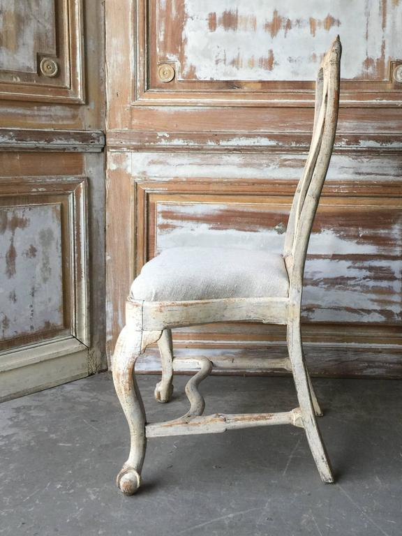 18th century Swedish chairs, in Rococo period circa 1760 with lovingly handmade rocaille carving on the seat rails and pierced splats. Hand scraped back to traces of their original worn cream paint, circa 1760, Göteborg, Sweden. Measures: Seat 14