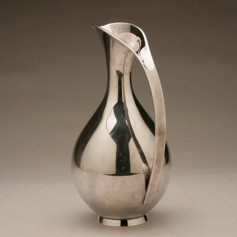 Anton Michelsen sterling silver pitcher by Kay Fisker.  Elegant slender, pear shaped pitcher with short spout extending downward and a loop handle that extends to the base. Very good condition.  Hallmarked from the 1950s with 1.5 liter
