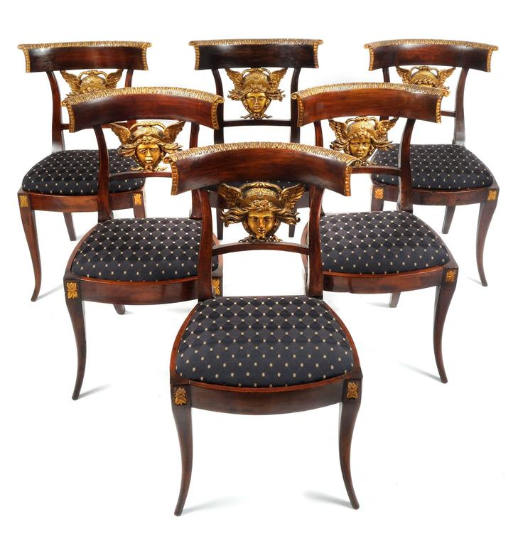 Set of six Italian (Lucca region) neoclassical carved klismos side chairs, circa 1810-1820. The splat of each chair features a stylized carved giltwood head of Medusa, each with slight variations of expression.   The Medusa has been immortalized in