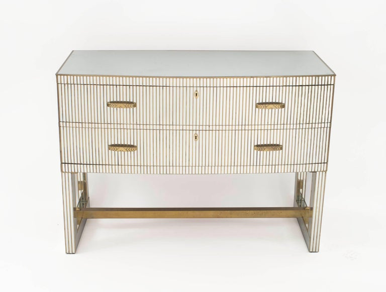 Pair of French midcentury (1950s) bow front mirrored chests with two drawers having a fluted bronze trim design with bronze handles and a bottom stretcher.