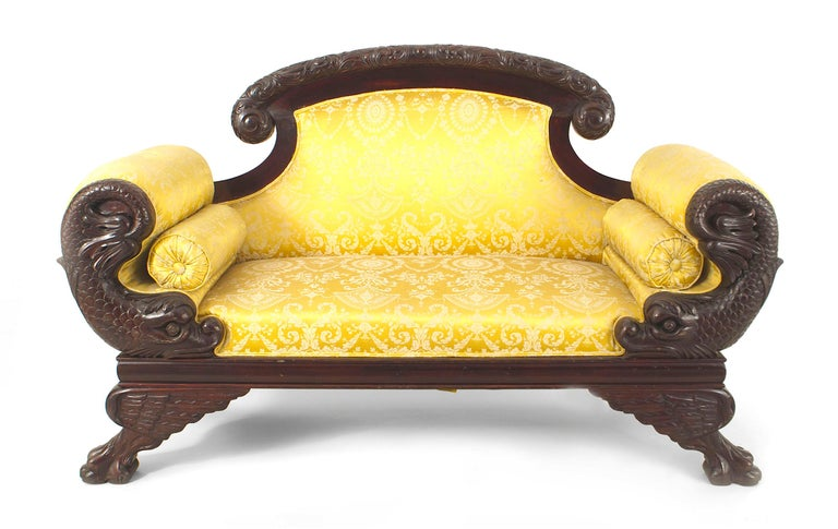 American Victorian mahogany carved dolphin-side roll arm loveseat with gold upholstery.