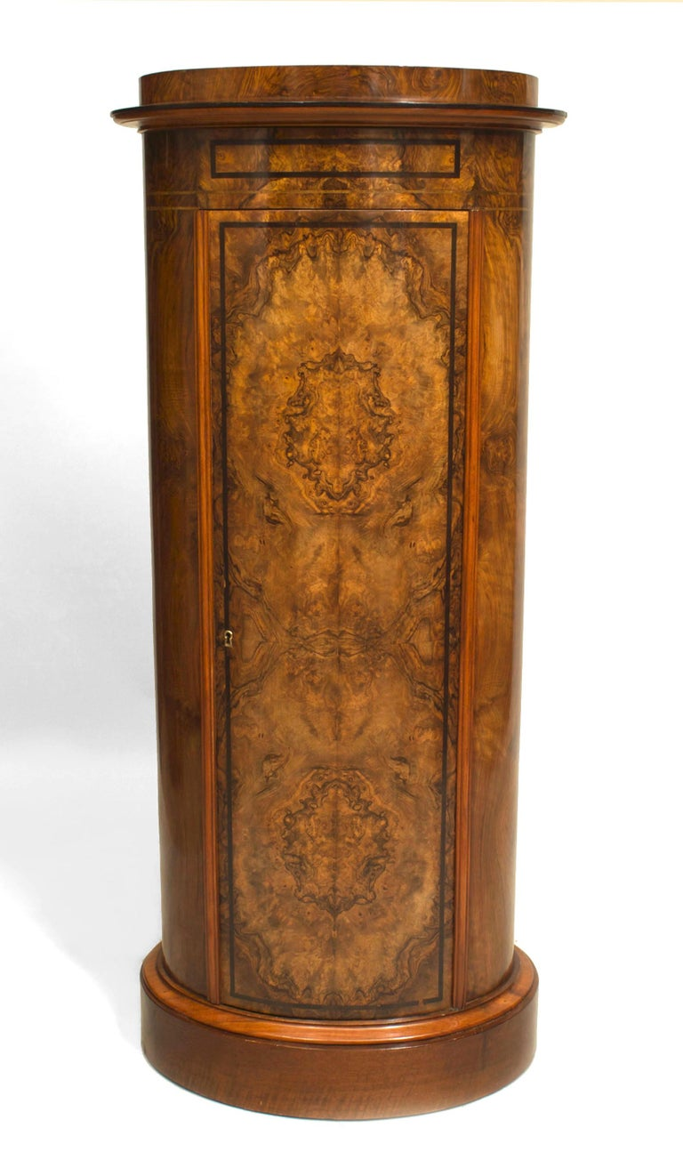 Nineteenth century Biedermeier pedestal cabinet originating in Austria or Germany. The tall, oval burl walnut cabinet has a flat back and is decorated with ebonized banded trim, which outlines a large front door that opens to reveal a set of three