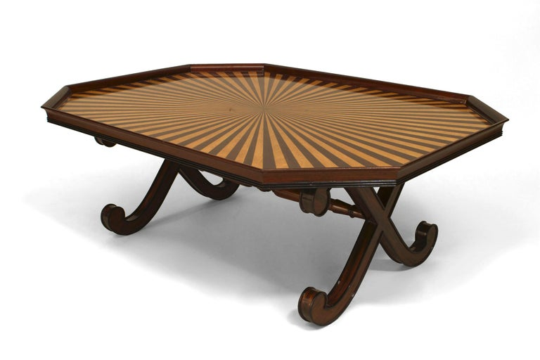 Twentieth century English Regency style mahogany coffee table featuring a double x-form base joined by a stretcher and supporting a hexagonal tray top inlaid with a vivid maple and mahogany sunburst design.